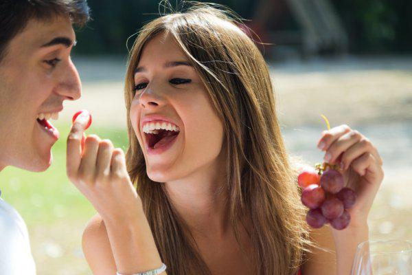 depositphotos_52776645-stock-photo-young-couple-eating-grapes-on