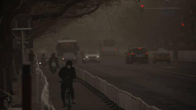 beijing-china-15-03-2021-people-ride-bicycles-in-the-street-as-the-area-is-hit-by-sandstorm-in-beijing-china-15-march-2021-according-to-the-national-meteorological-center-floating-sand-and-dust-are-expected-to-swee