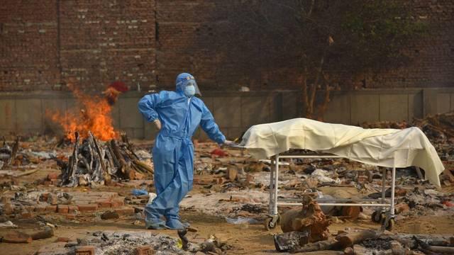 ea4468-nueva-delhi-india-29-04-2021-un-indio-vestido-con-un-traje-epi-espera-junto-a-una-camilla-donde-yace-el-cadaver-de-un-familiar-en-un-campo-crematorio-para-victimas-de-la-covid-19-este-jueves-en-nueva-delhi-e